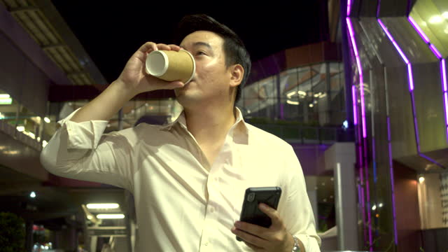 handsome young businessman drink a coffee and use smart phone in the city at night. - coffee drink stock videos & royalty-free footage