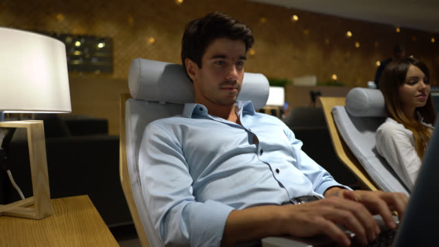 handsome young businessman relaxing at the airport's vip lounge working on laptop - gate stock videos & royalty-free footage