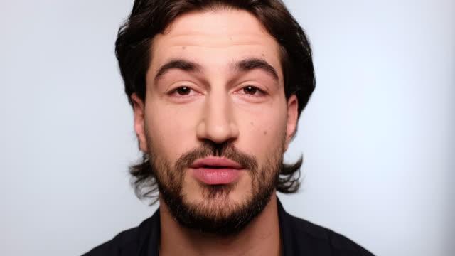 stockvideo's en b-roll-footage met knappe jonge kerel praat en glimlachend - eenvoud