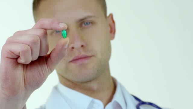 vídeos y material grabado en eventos de stock de atractivo joven médico de pasar pastillas - píldoras