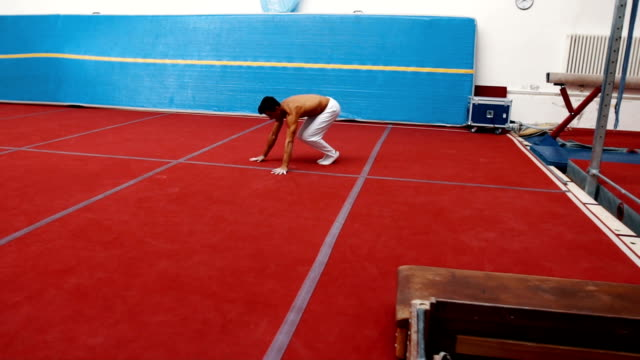 Handsome young male gymnast training on sport mat