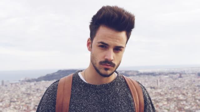 vídeos de stock e filmes b-roll de handsome young male tourist against cityscape - homens jovens