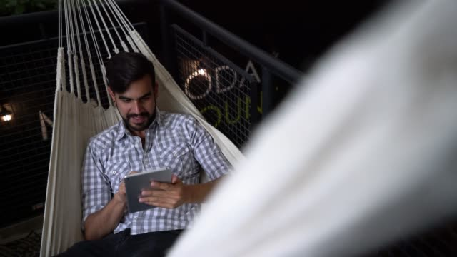 Handsome young man at a creative office relaxing on a hammock while checking his social media on tablet