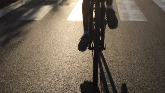 handsome young man cycling on the road at sunset - helmet stock videos & royalty-free footage