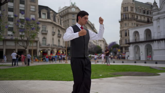 handsome young man dancing tango alone on a town square - tangoing stock videos & royalty-free footage
