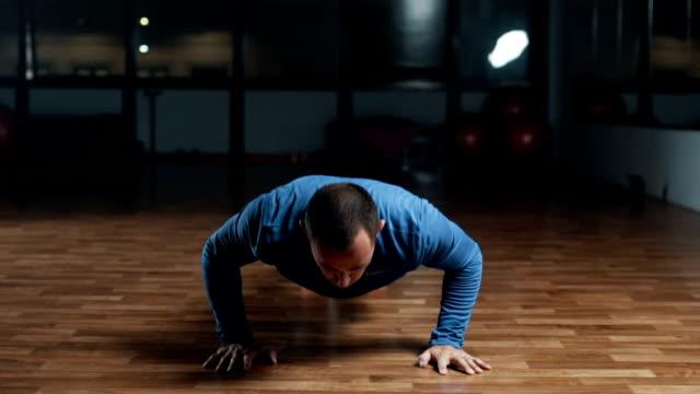 vídeos de stock e filmes b-roll de handsome young man doing intense push ups - flexão de braço