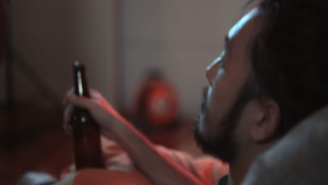 handsome young man drinking beer at party - substance abuse stock videos & royalty-free footage