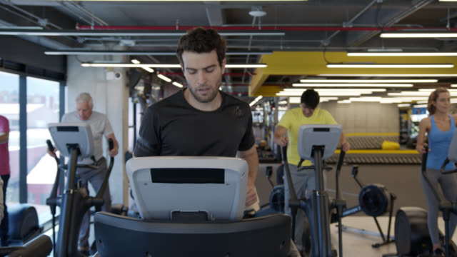 handsome young man running on treadmill while other people exercise on other machines at the gym - cross trainer stock videos & royalty-free footage
