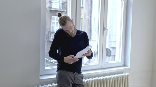 handsome young man standing by the window and having a phone conversation - junger mann allein stock-videos und b-roll-filmmaterial