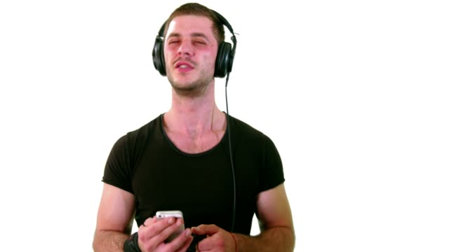 handsome young man standing in front of a white studio background and listening to music - cantare video stock e b–roll