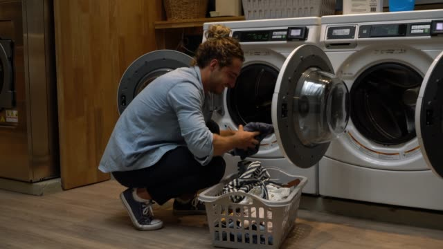 handsome young man taking out the clothes from a drying machine and putting them in a laundry basket smiling at a laundromat - laundry basket stock videos and b-roll footage