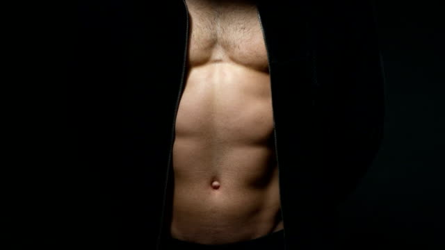 handsome young man with good muscles in a cape over a black background - torso stock videos & royalty-free footage