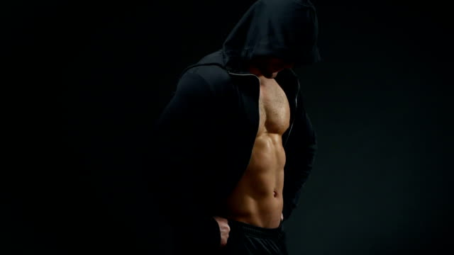 handsome young man with good muscles in a cape over a black background - males stock videos & royalty-free footage