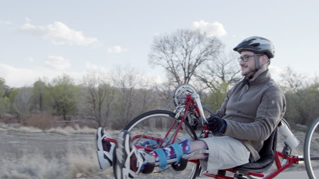 vídeos de stock e filmes b-roll de slow motion shot of a handsome young man passing by the camera on a red handcycle wearing orthotic leg braces for adaptive exercise outdoors in the spring - accessibility