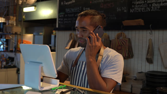 handsome young waiter registering a delivery on system while talking to customer on phone - order stock videos & royalty-free footage