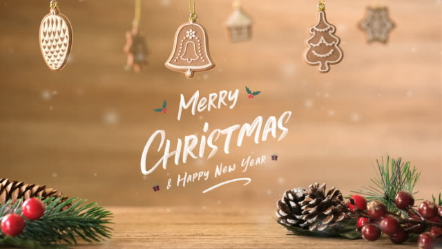 Handwriting Merry Christmas and happy new year at Christmas tree and mistletoe leaf and pine cone on wooden table with snow fall.winter holiday seasonal greeting card