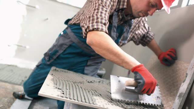 handyman kleberauftrag auf einer fliese. - renovierung konzepte stock-videos und b-roll-filmmaterial