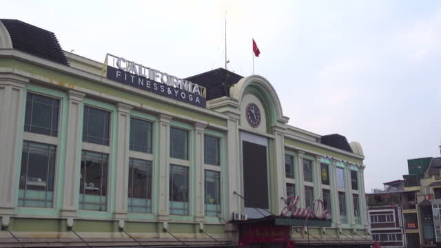 hang da market building exterior at hanoi vietnam. vietnamese flag and clock - traditionally vietnamese stock videos & royalty-free footage