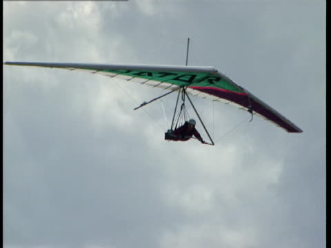 a hang glider flies in a cloudy sky. - hang gliding stock videos & royalty-free footage