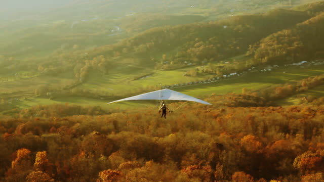 hang glider flying freely in the mountain valley - hang gliding stock videos and b-roll footage