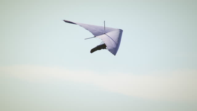 Hang glider in the air turning right then left.