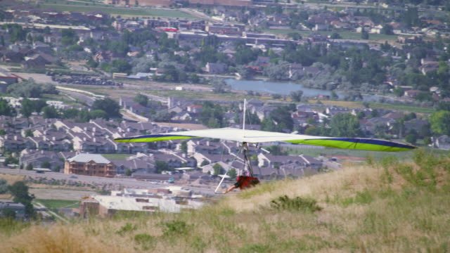Hang glider is taking off from hill overlooking South Salt Lake valley in Utah.