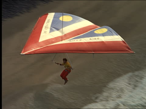 aerial hang glider over mountainous coastline - hang gliding stock videos and b-roll footage