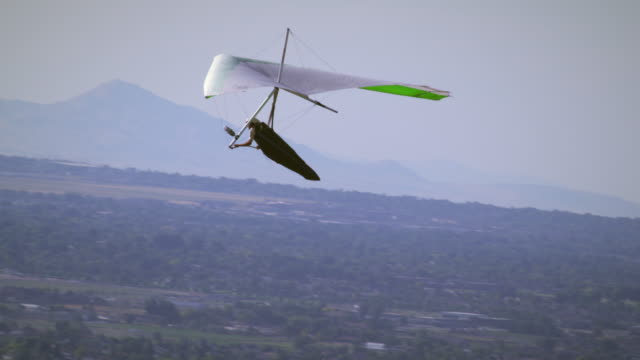 Hang glider soaring through air with valley and mountains seen in distance.