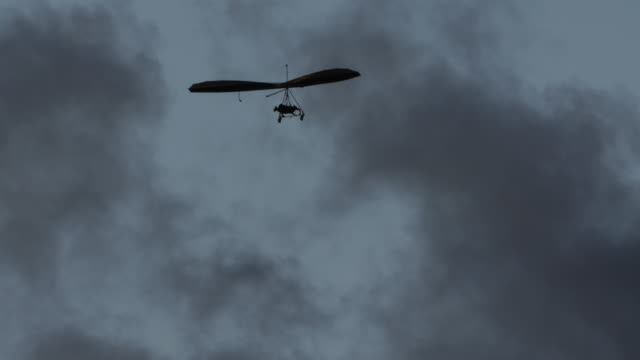 hang gliding flying in cloudy day - hang gliding stock videos and b-roll footage