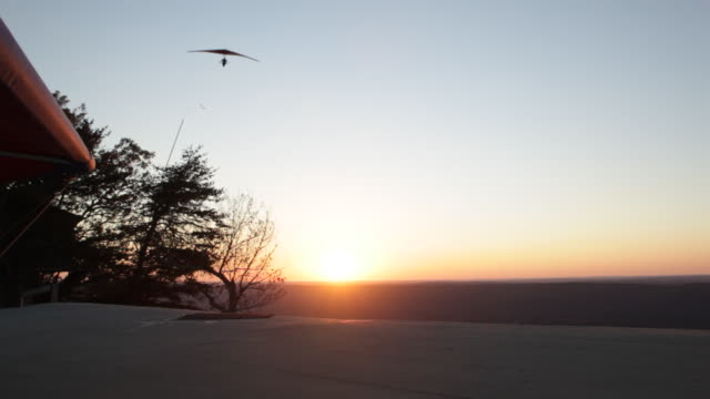 Hang Gliding Flying over Summit at Sunset