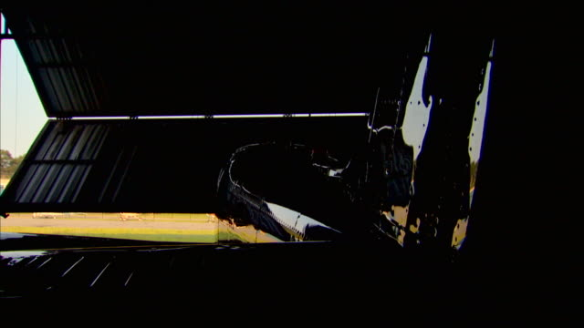 a hangar door opens to reveal a glossy small prop plane. - hangar stock-videos und b-roll-filmmaterial