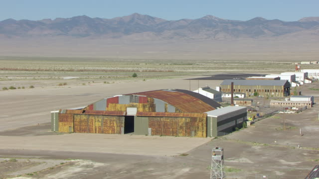 MS AERIAL DS hangar entrance at Wendover airfield with mountains / Wendover, Utah, United States