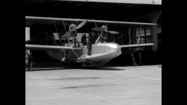 INT hangar with PN9 flying boat and mechanics / technicians at engine propeller wings / PN9 emerges from hangar into sunlight ground crew guides it...