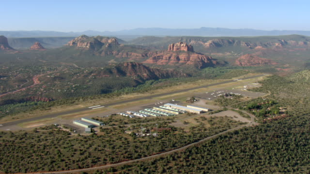 hangars line the runway of the sedona airport in arizona. - 飛行機格納庫点の映像素材/bロール