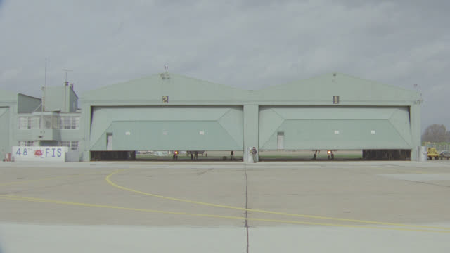 2 hanger doors open; 2 - f-15's emerge, taxi out, to & by camera - 飛行機格納庫点の映像素材/bロール