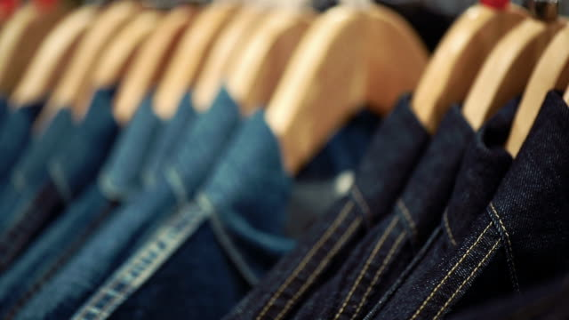 hangers with a fashionable jeans clothes in store boutique - shopping discounts - rack stock videos & royalty-free footage