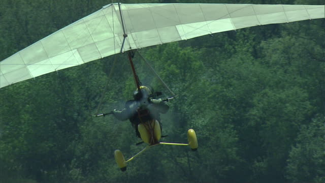 A hang-glider above a river and fields.