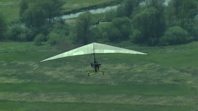a hang-glider above green areas. - hang gliding stock videos & royalty-free footage