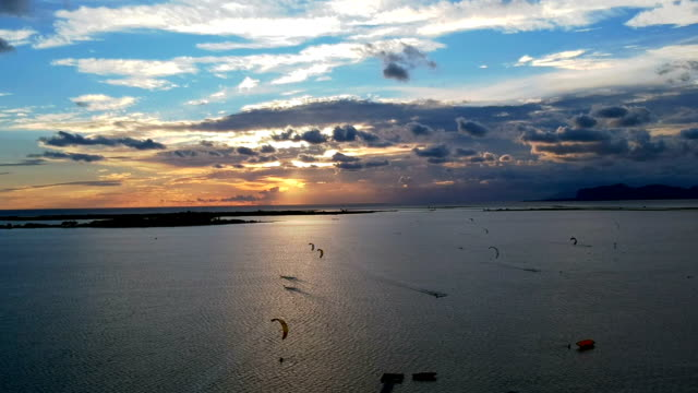Hang-gliders flying above coast. Sea sunset. Aerial view