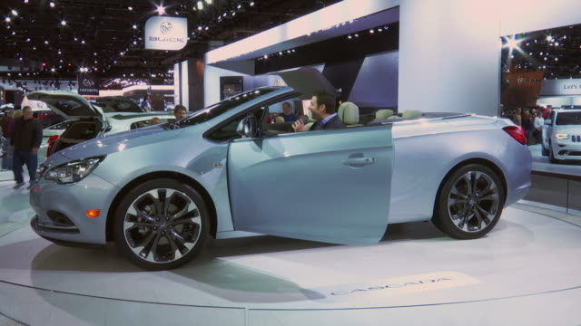 ws hanging buick sign zows cascada revolving on turntable / cu front end / ws narrator puts retractable roof up and then back down / cu dashboard... - 乗り物の明かり点の映像素材/bロール