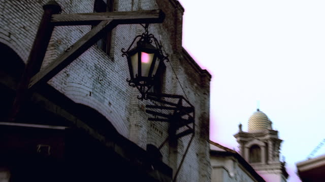 vidéos et rushes de zi hanging lantern outside olvera street vendor's booth with bell tower of old plaza church beyond and some unnatural coloring / los angeles, california, united states - procédé croisé