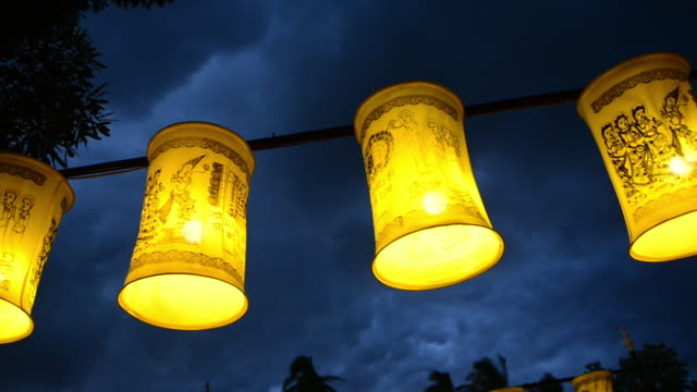 hanging lanterns swaying in the wind at the bridge leading to wat traphang thong - wind点の映像素材/bロール