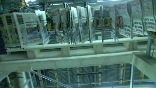 vídeos y material grabado en eventos de stock de hanging newspapers moving overhead on conveyor system, rotate underneath, warehouse machines w/ elaborate conveyor system above, jacket on table fg,... - máquina impresora