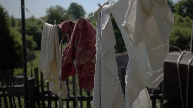 hanging on a clothesline in front of sun - washing stock videos and b-roll footage