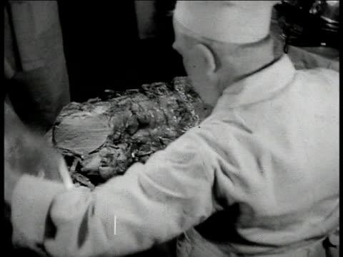 vídeos y material grabado en eventos de stock de hanging side of beef roasting hand w/ ladle pouring juice over cooking meat ots man in chef's hat carving roast possibly mutton cu hands placing tray... - carne de vaca