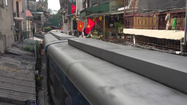 hanoi iconic street crossed by a train. vietnam red flags. high angle view of trần phú street. hoàn kiếm district - hanoi stock videos and b-roll footage