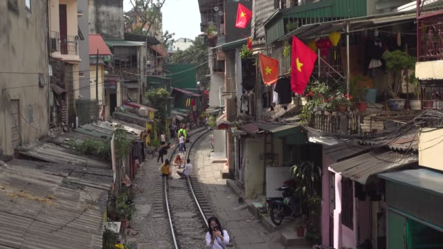 hanoi iconic train street high angle point of view. tourists taking pictures. vietnam red flags. trần phú street. hoàn kiếm district - hanoi stock videos and b-roll footage