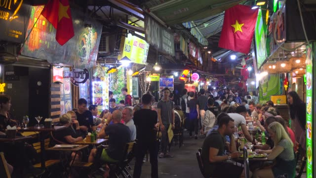 hanoi old quarter nightlife with vietnamese flags during tet celebration. hoan kiem old town district street full of restaurants with tourists and locals - traditionally vietnamese stock videos & royalty-free footage