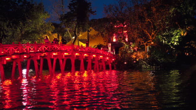 vídeos de stock, filmes e b-roll de hanoi red bridge and ngoc son temple illuminated. people crossing cau the huc bridge above hoan kiem lake at night. vietnam during tet celebration - newly industrialized country
