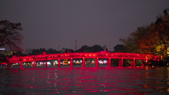 vídeos de stock, filmes e b-roll de hanoi red bridge illuminated. people crossing cau the huc bridge above hoan kiem lake at night. vietnam during tet celebration - newly industrialized country